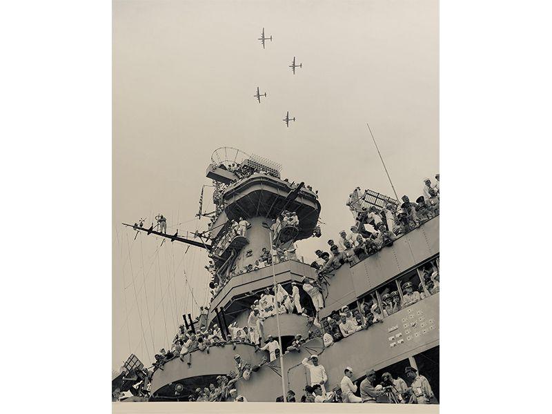 sailors watch as B-29 bombers fly overhead